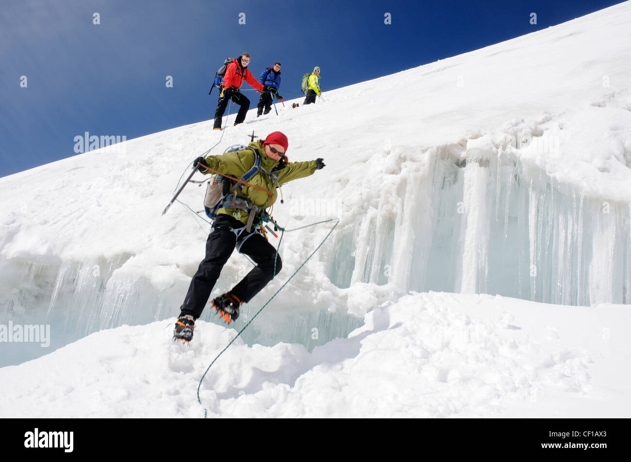 A lady climber leaping a large crevasse on the traverse on Monte Rosa in Switzerland - Stock Image