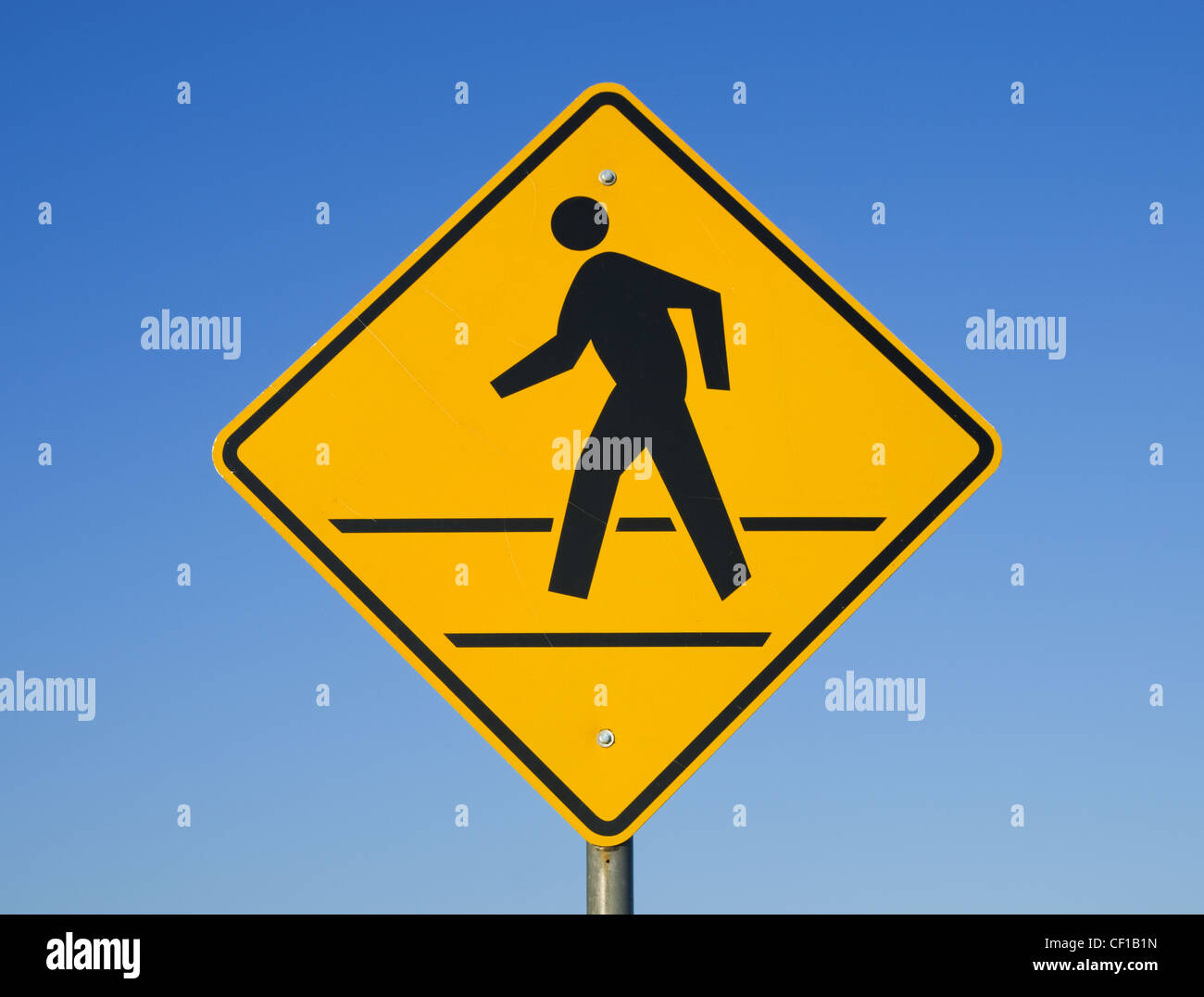 crosswalk sign with a man walking on yellow with a blue sky background - Stock Image