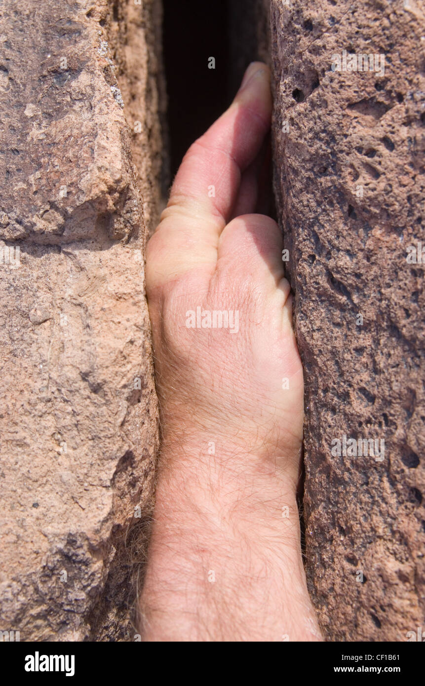 hand jam rock climbing hold in a crack - Stock Image