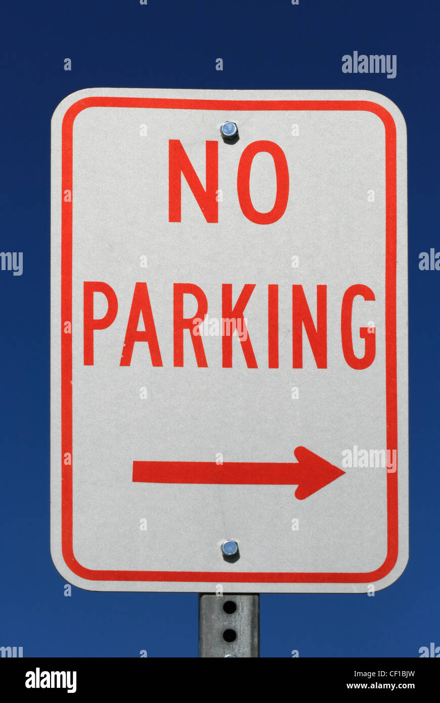 red and white no parking sign with an arrow and blue sky background - Stock Image
