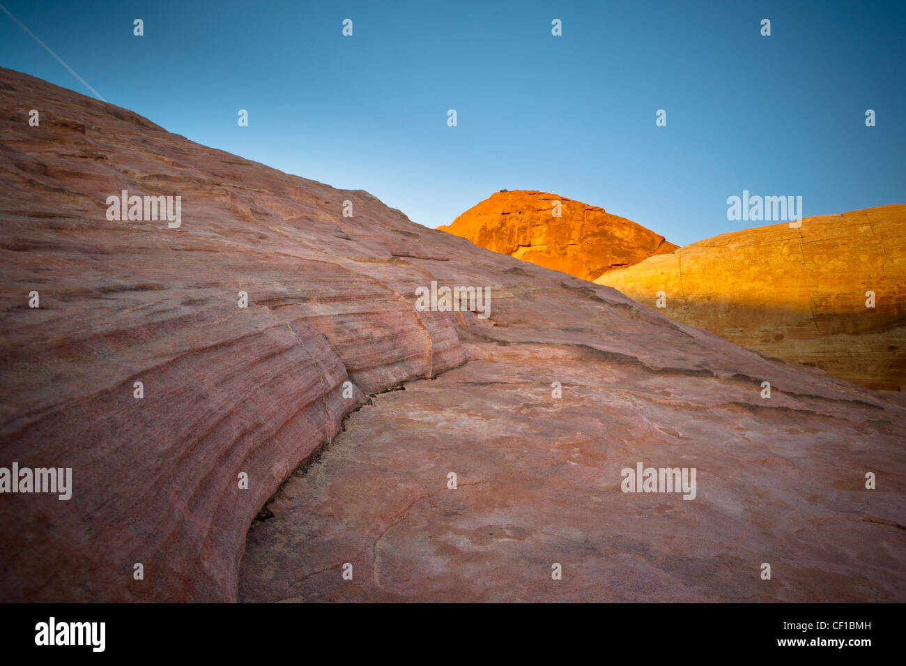 Sunlight Shining On Red Rock With A Blue Sky Above; Nevada United States Of America - Stock Image