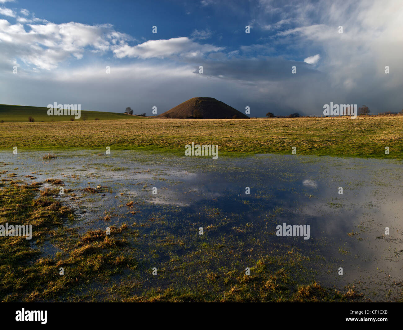 Silbury Hill, the tallest prehistoric human-made mound in Europe, viewed across a flooded field. - Stock Image