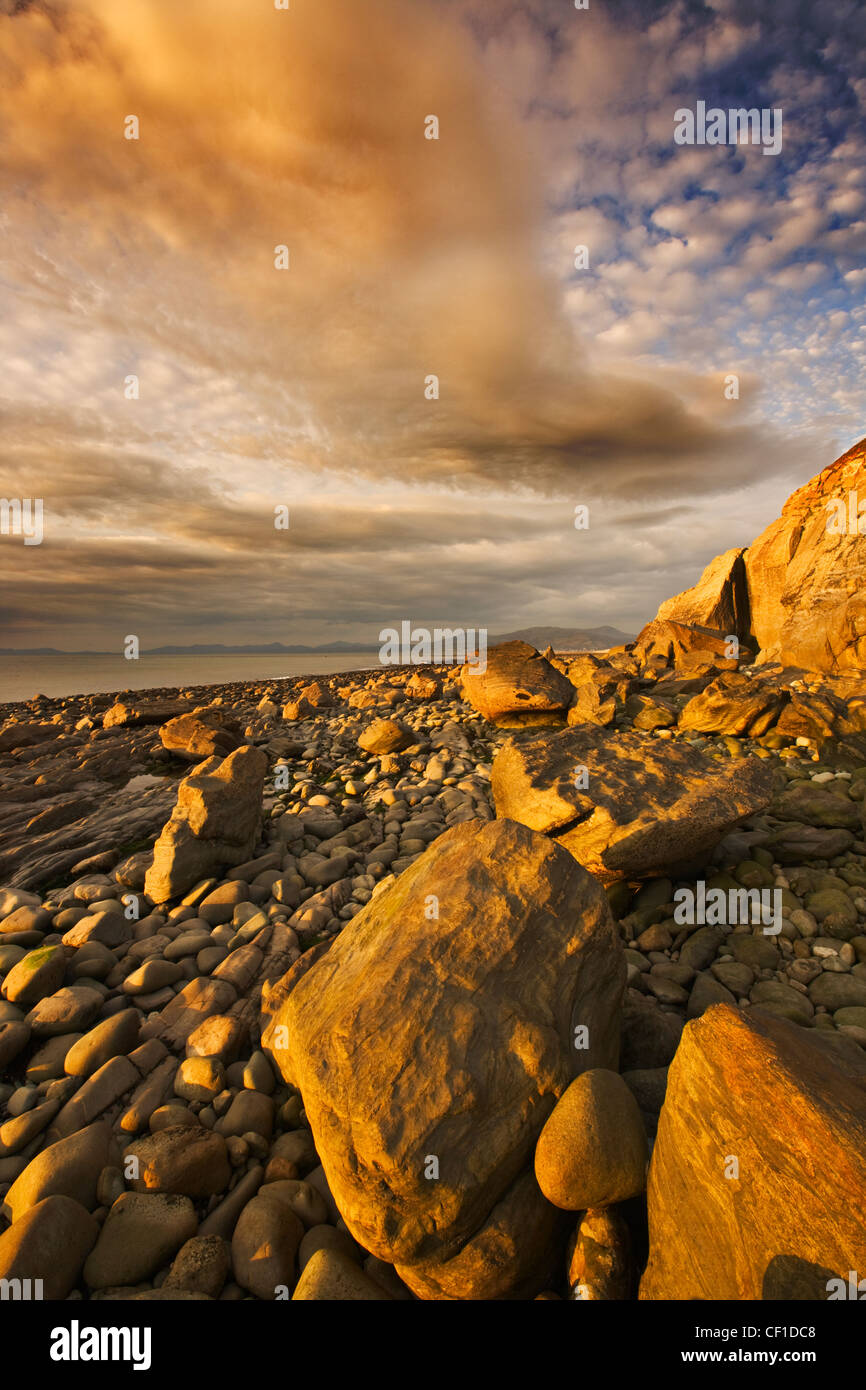 Storm light over a stoney beach near Llwyngwril in the Snowdonia National Park. Stock Photo