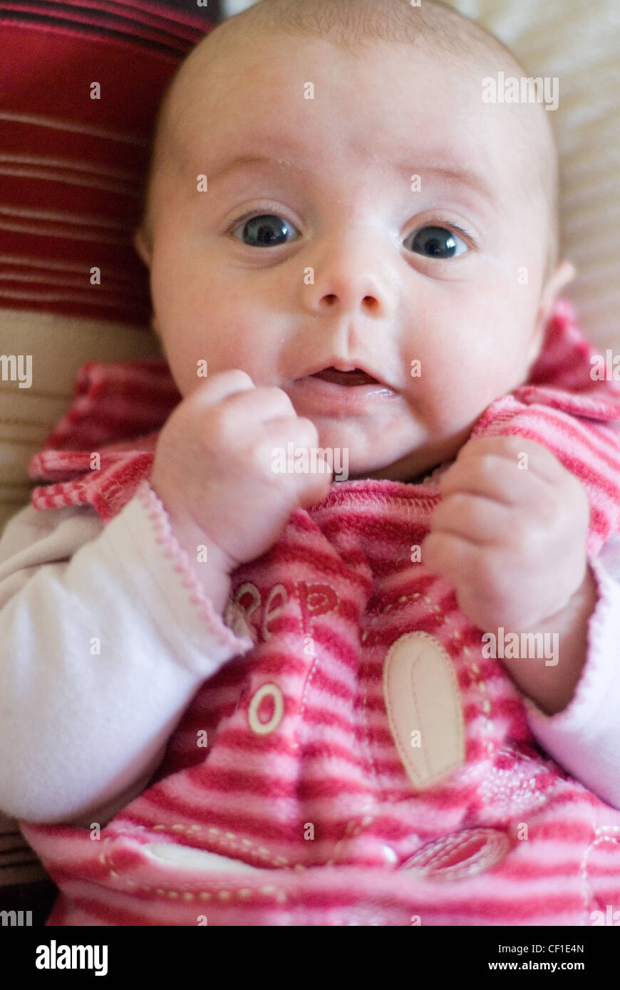 A Two Month Old Female Dressed In A Pink Striped Fleece Babygrow