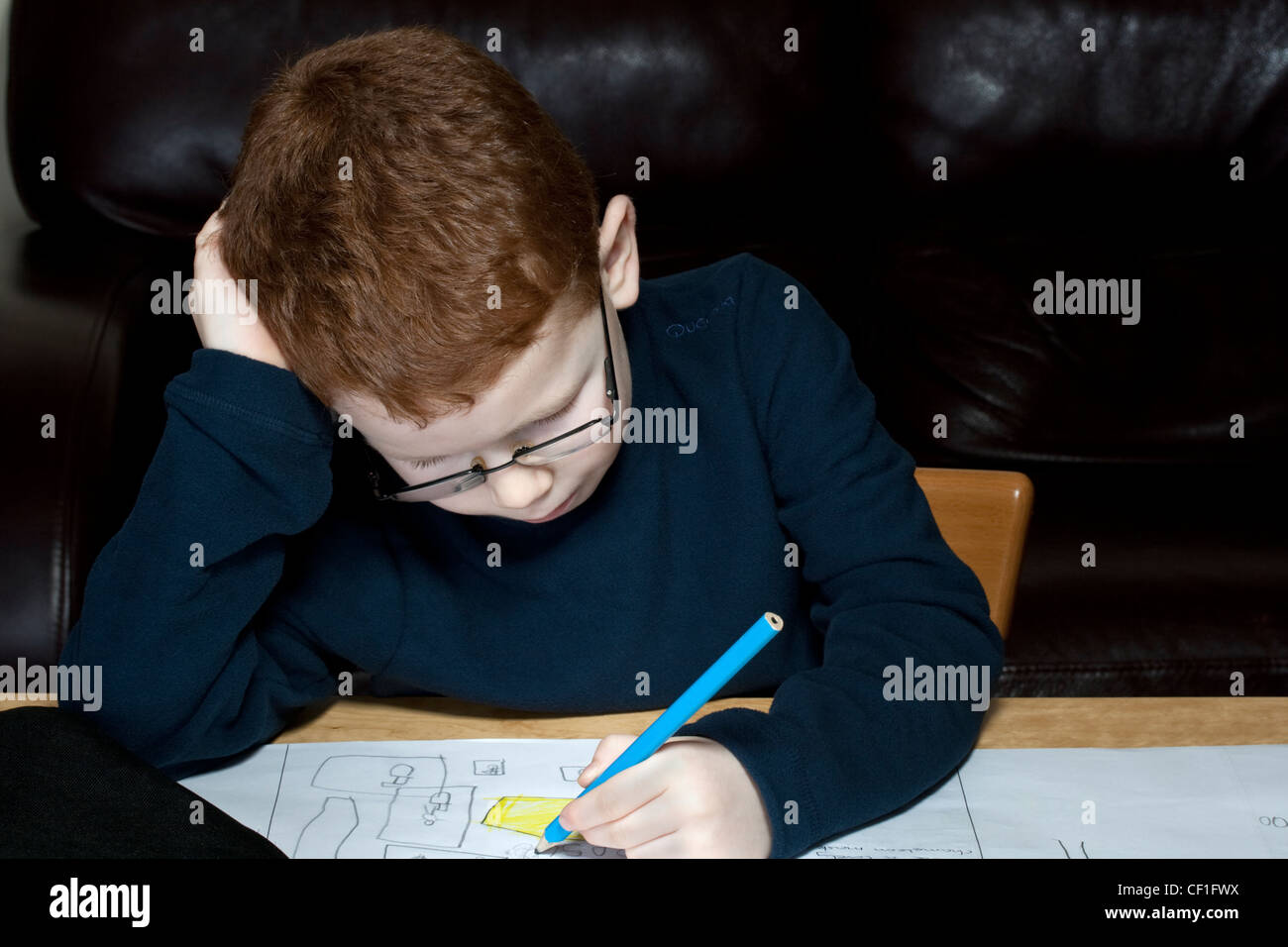 Left handed six year old child writing in a school book - Stock Image