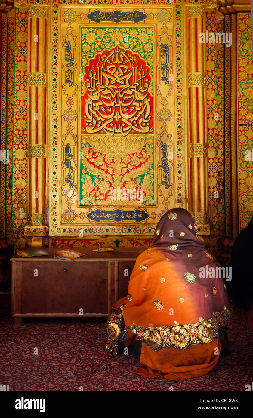 A  muslim woman praying in front of  the Mausoleum of the Sufi saint Nizamuddin Auliya (Nizamuddin Dargah), Delhi, Stock Photo