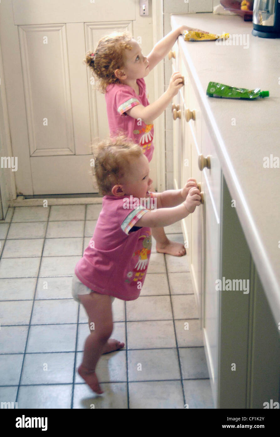 Female children with curly red hair, wearing matching pink t shirts, standing in the kitchen - Stock Image