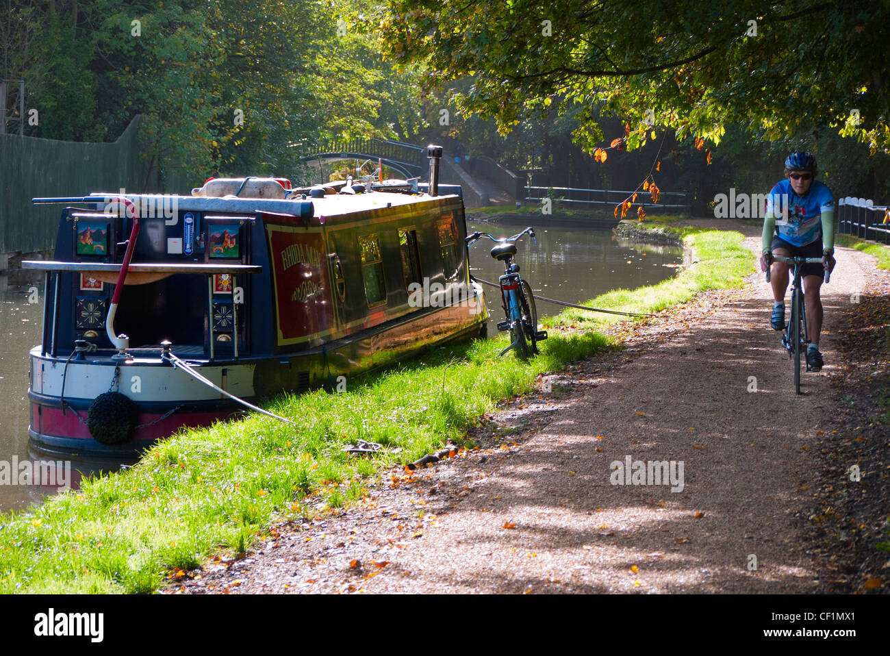 A cyclist riding along the towpath past a houseboat on Oxford Canal in Autumn. - Stock Image