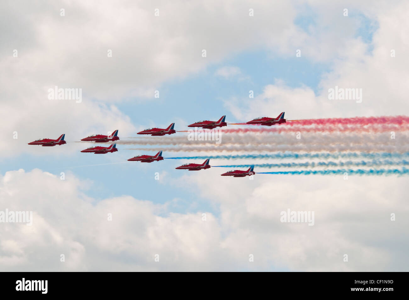 The Red Arrows aerobatic display team in formation during a level flypast. - Stock Image