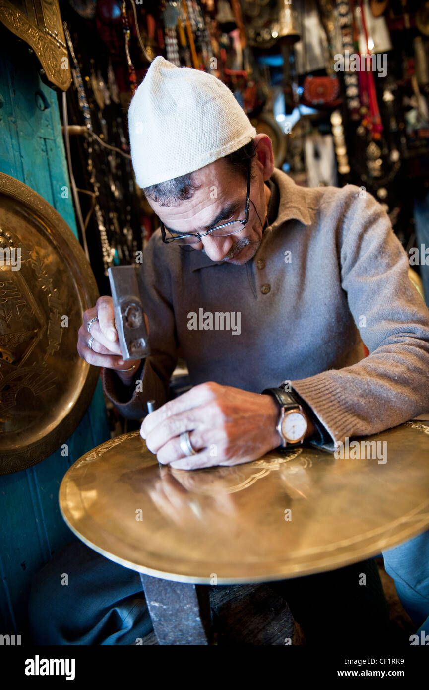 Local artisan hammering metal in his shop of Chefchaouen, Morocco - Stock Image