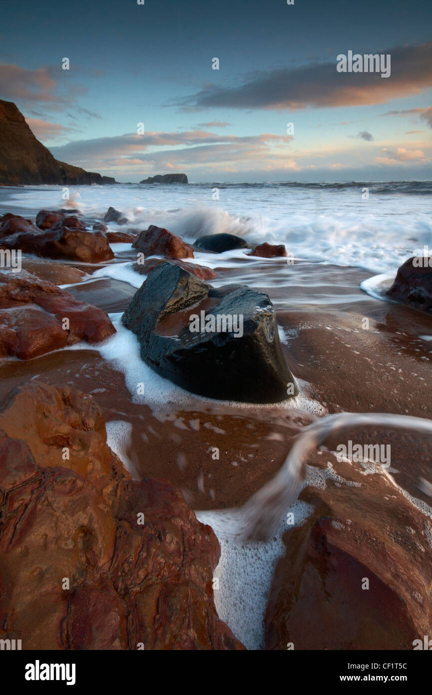 The tide flowing onto the beach at Saltwick Bay. - Stock Image