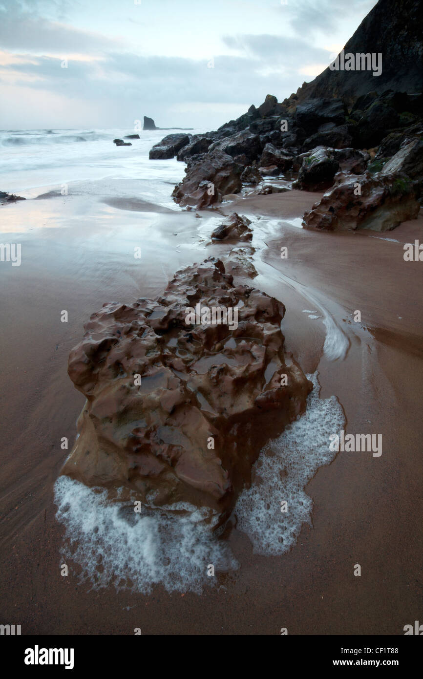 Pools of water formed by the ebbtide around rocks on the beach at Saltwick Bay. - Stock Image