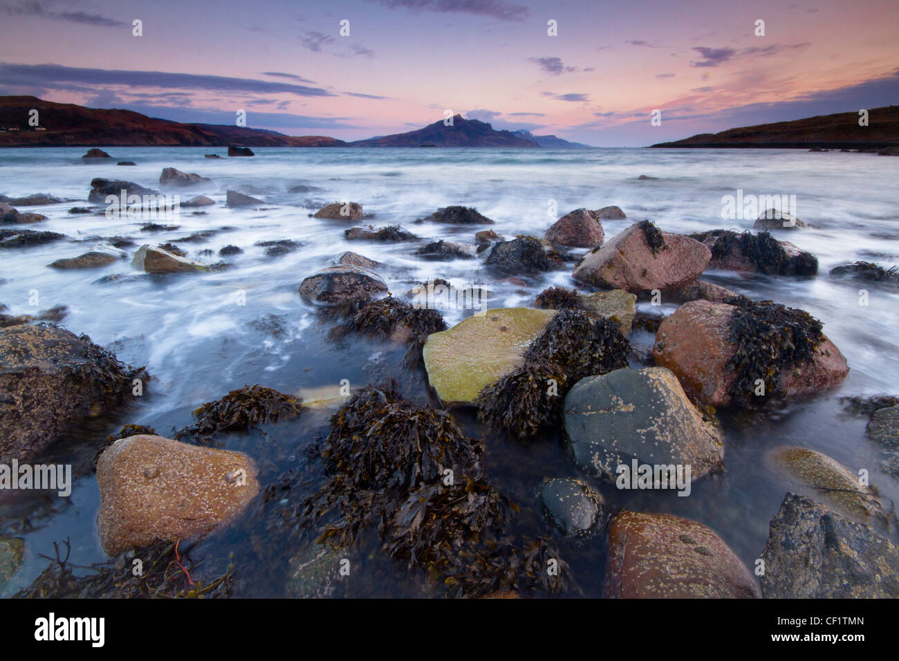 The sea lapping around rocks on the shore at Balmeanach a quiet crofting township near Dunvegan on the Isle of Skye. - Stock Image