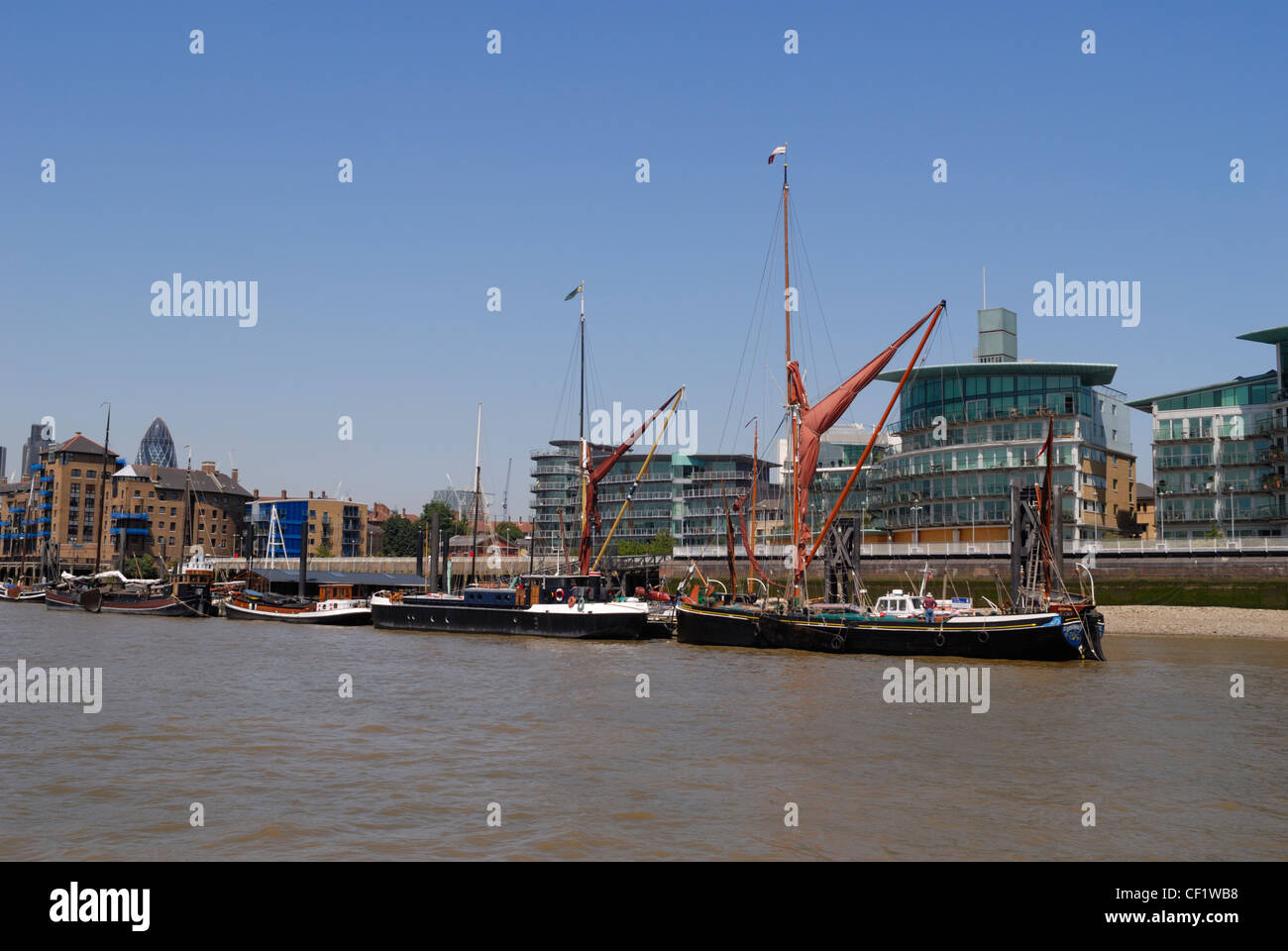 Old Thames sailing barges beside modern, luxury apartments on the river Thames. - Stock Image