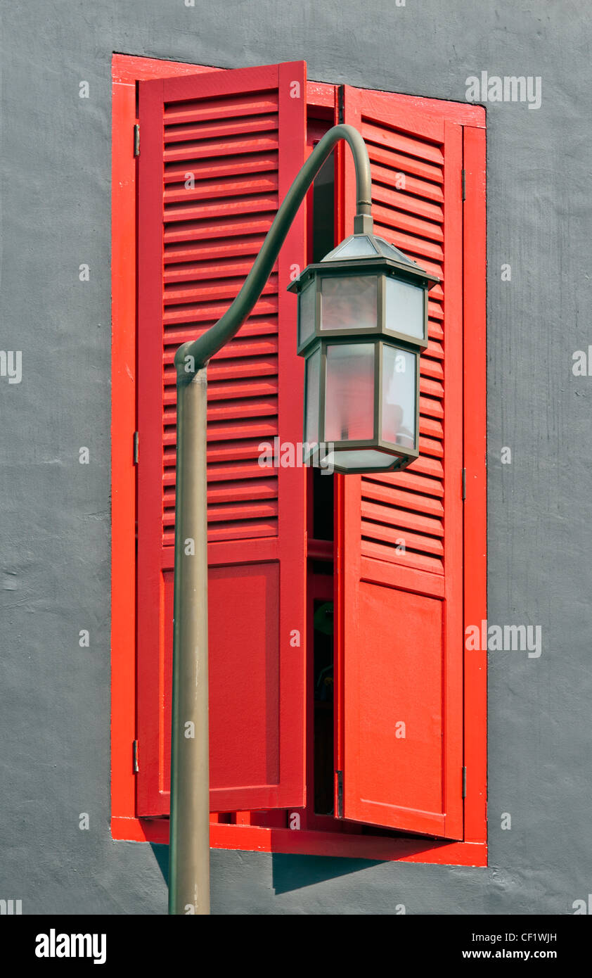 Closeup of streetlamp and red shuttered window - Stock Image