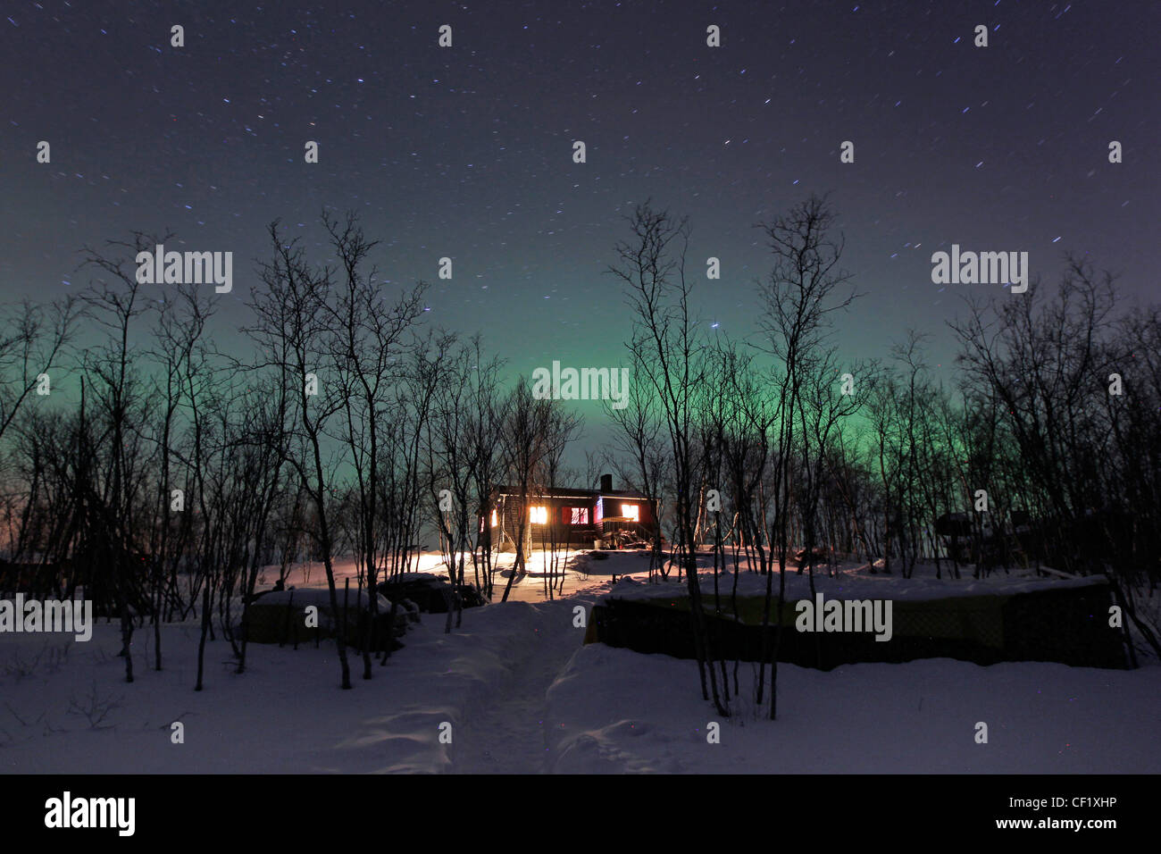 Aurora Borealis, Northern Lights, shine over a home in Abikso, northern Sweden - Stock Image