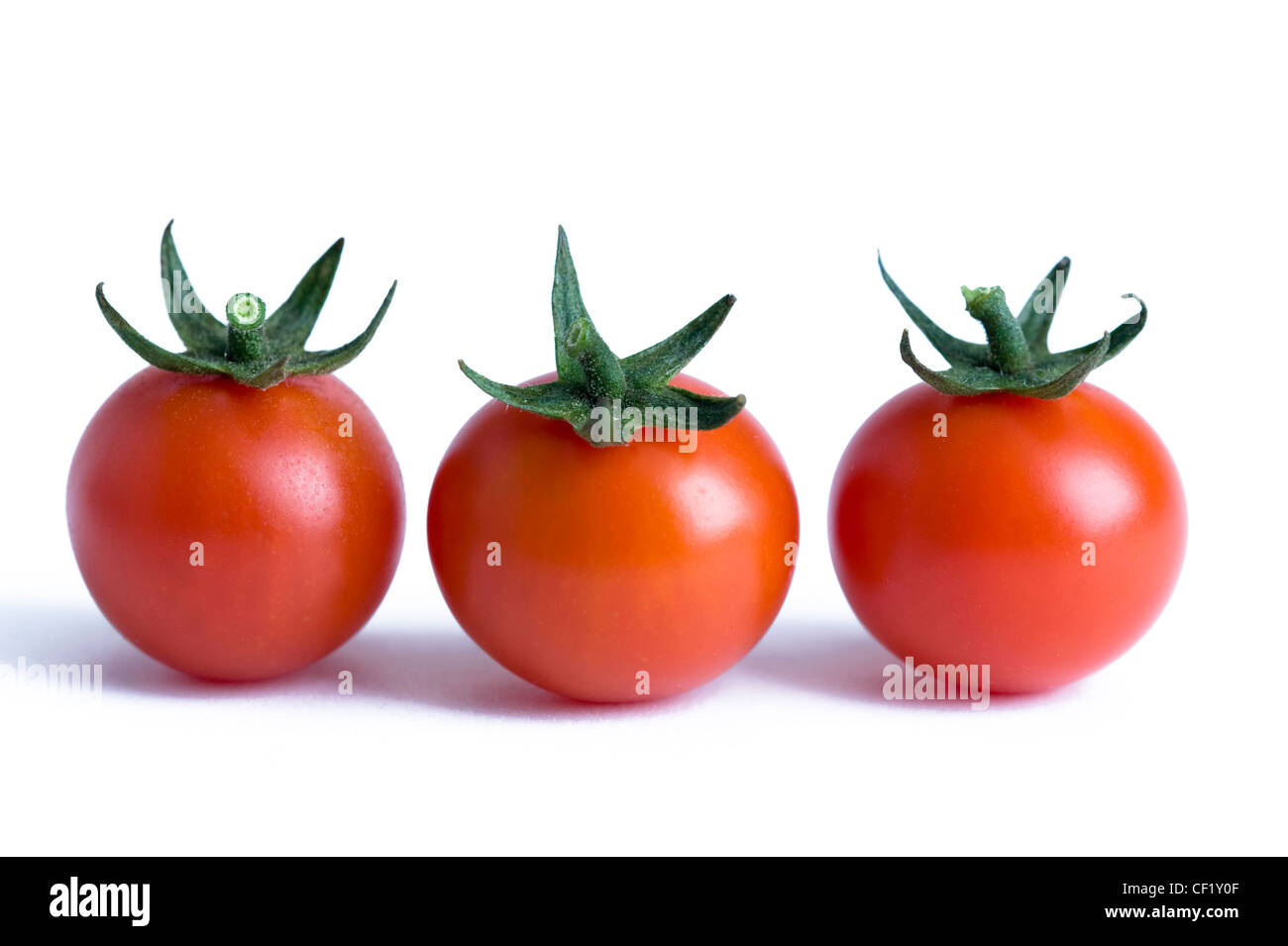three cherry tomatoes isolated on a white background - Stock Image