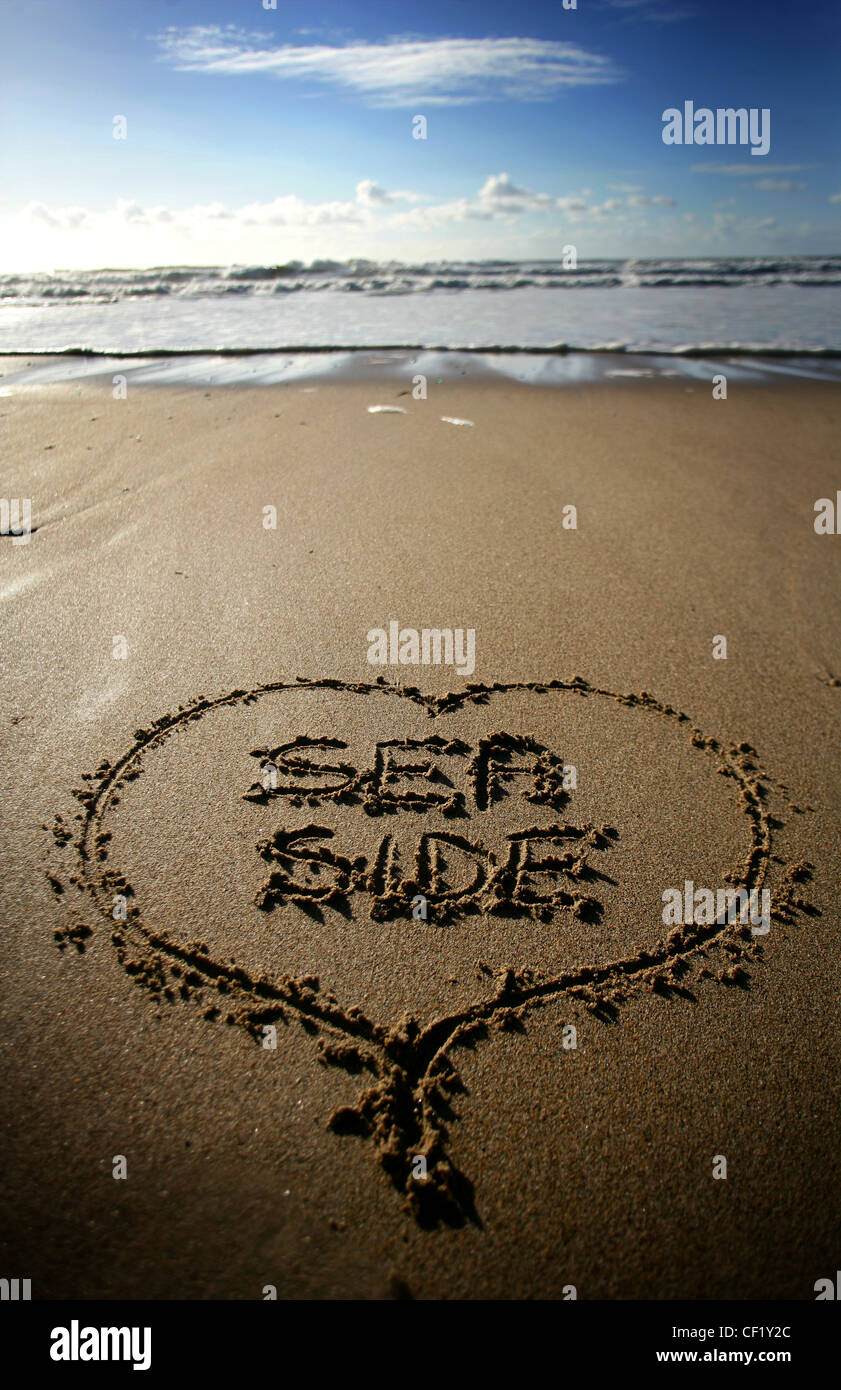 Writing in the sand at Praa Sands. A huge sandy beach popular with families and surfers. - Stock Image