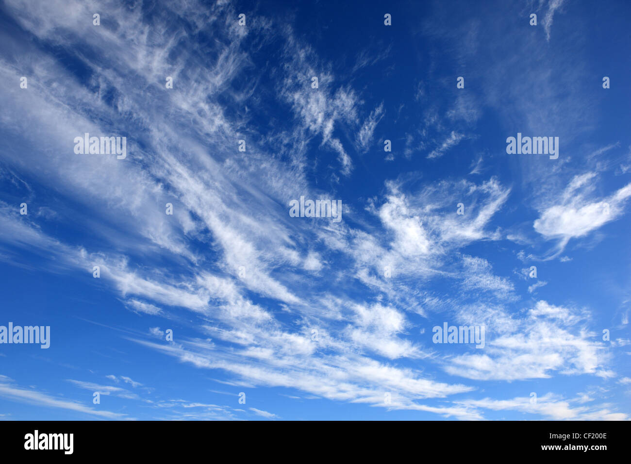 White wispy clouds in a blue summer sky - Stock Image