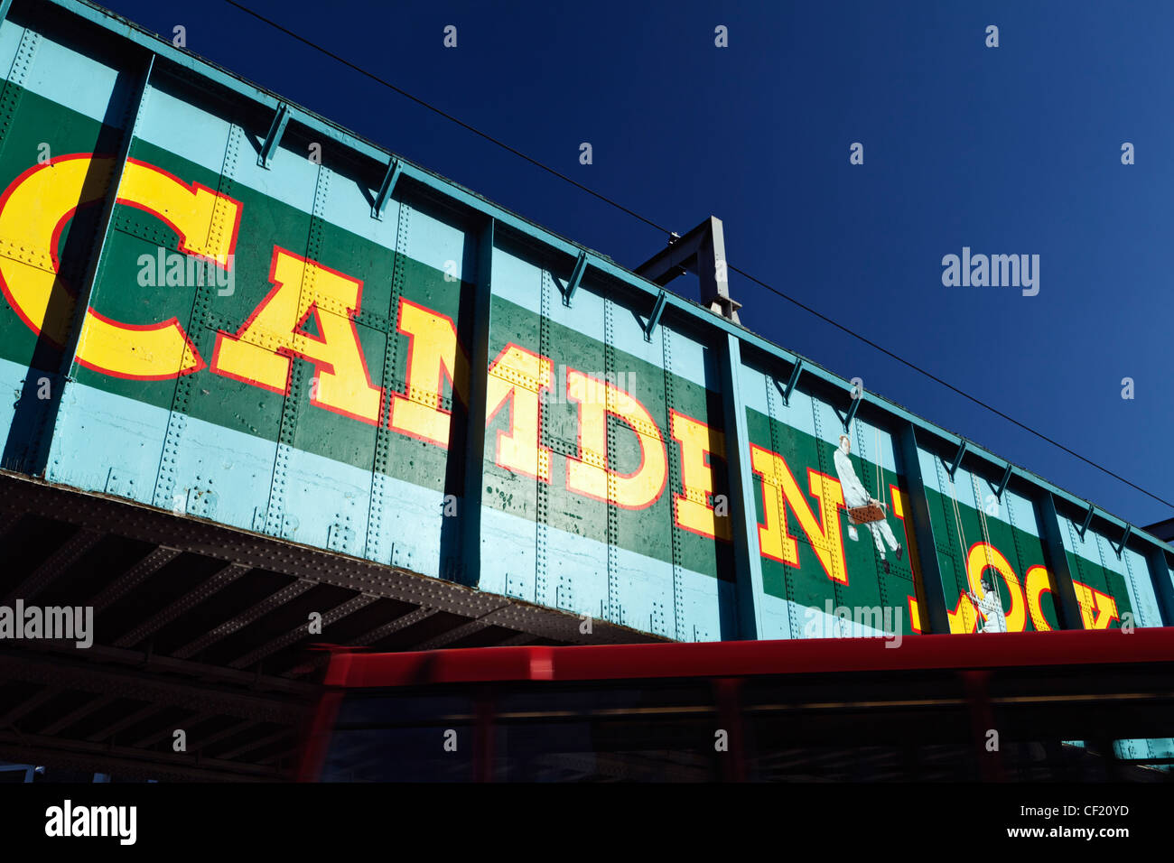 A red double decker bus passing under the old railway bridge over Chalk Farm Road at Camden Lock. The bridge features Stock Photo