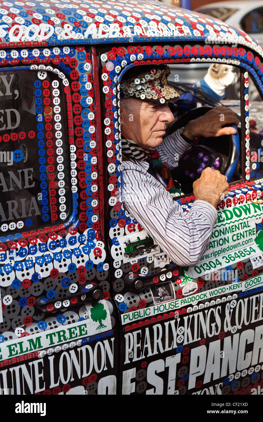 A taxi driver in a Pearly Kings and Queens decorated London taxi cab. - Stock Image