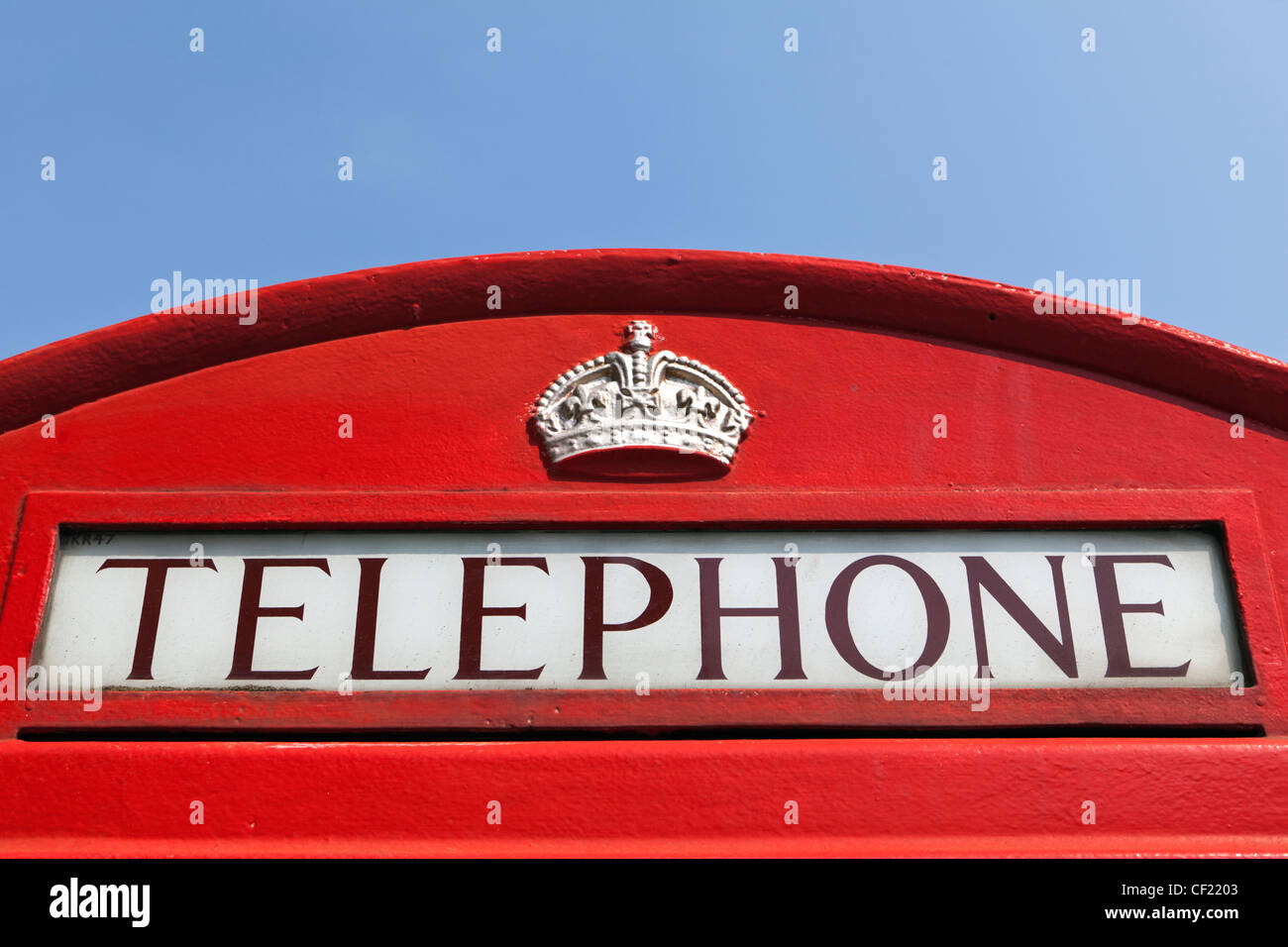 The top of a red telephone box featuring a crown and the word 'TELEPHONE'. - Stock Image