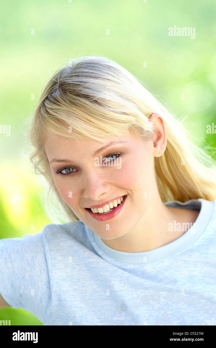 Female long straight blonde hair tucked behind ear wearing pale blue t shirt looking straight to camera smiling - Stock Image