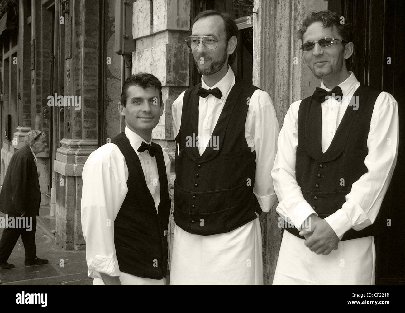 Three waiters of various sizes in B/W ( black and white) - Stock Image
