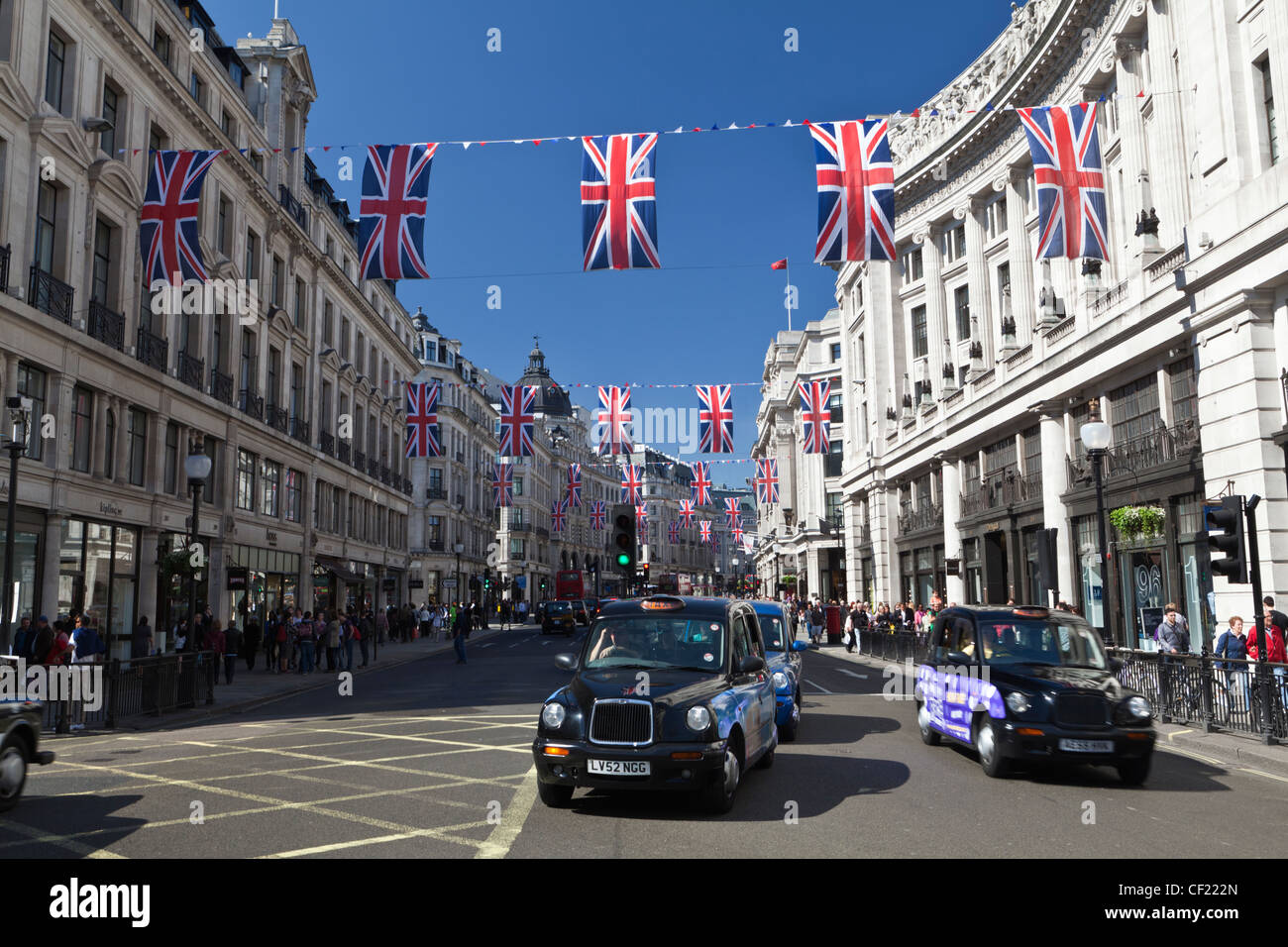 Taxi cabs in Regent Street under red, white and blue bunting strung across the street to celebrate the Royal Wedding - Stock Image