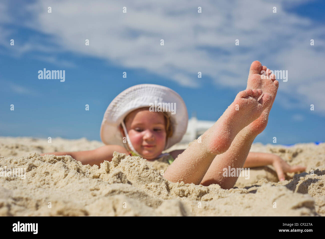 buy online ef4e1 8b075 A child throws sand in the air while playing on the beach. - Stock Image