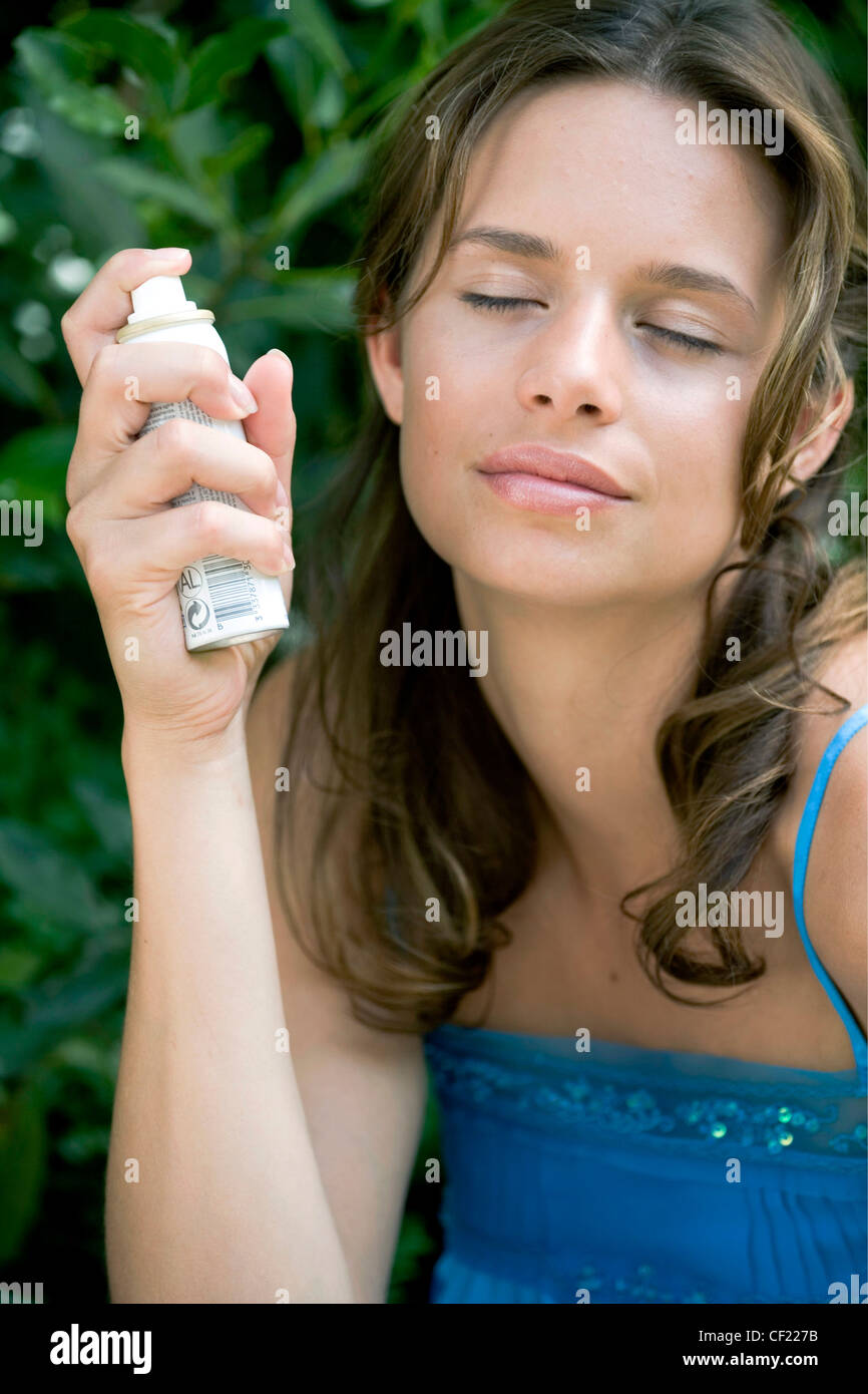 A DayYourself: Female long brunette hair tied back loosely wearing blue top holding small atomiser spray to side - Stock Image