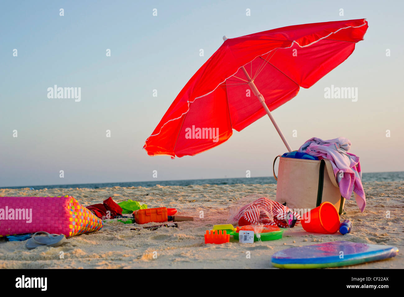 A single red umbrella sits on the beach surrounded by toys as the sun sets. - Stock Image