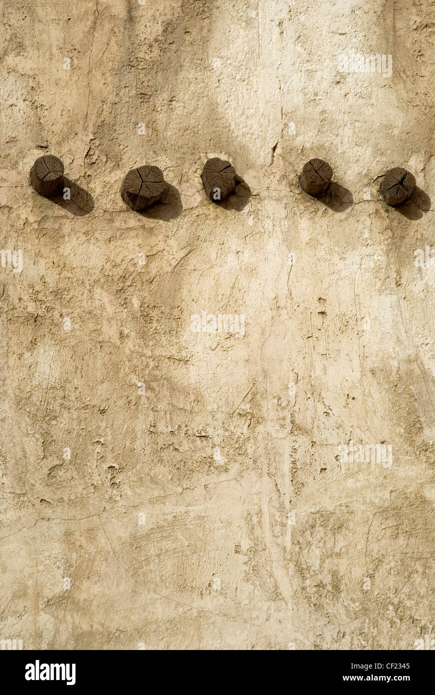 old weathered wall with joists protruding - Stock Image