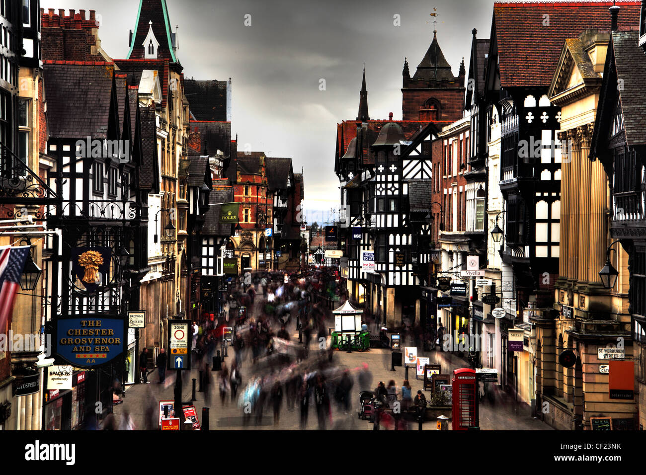Chester city shoppers rushing around and going about their business in Northgate Street where it meets Frodsham - Stock Image