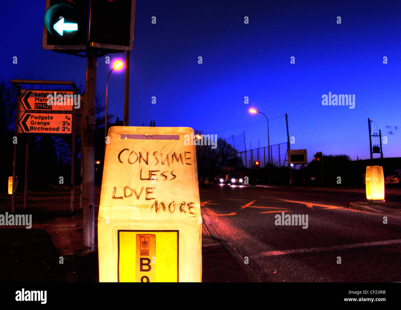 Comsume Less Love More scrawled on a road beacon, Padgate / Birchwood A57 Warrington at Dusk. - Stock Image