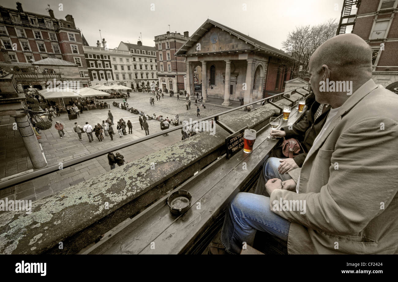 Drinking Beer in Covent Garden and overlooking old London and the square - Stock Image