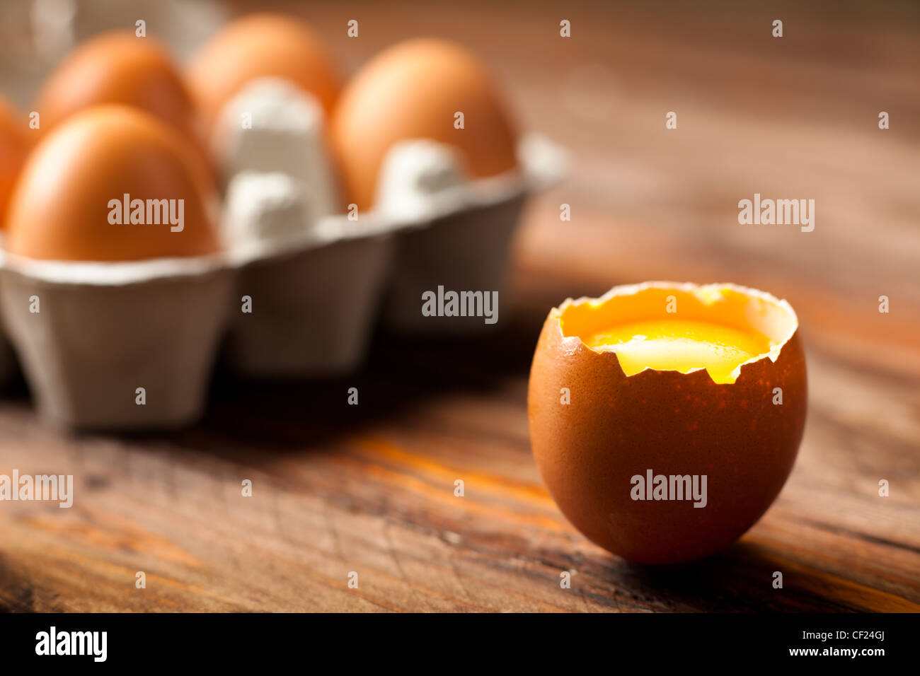 Opened Egg Shell with Yolk on Wood - Stock Image