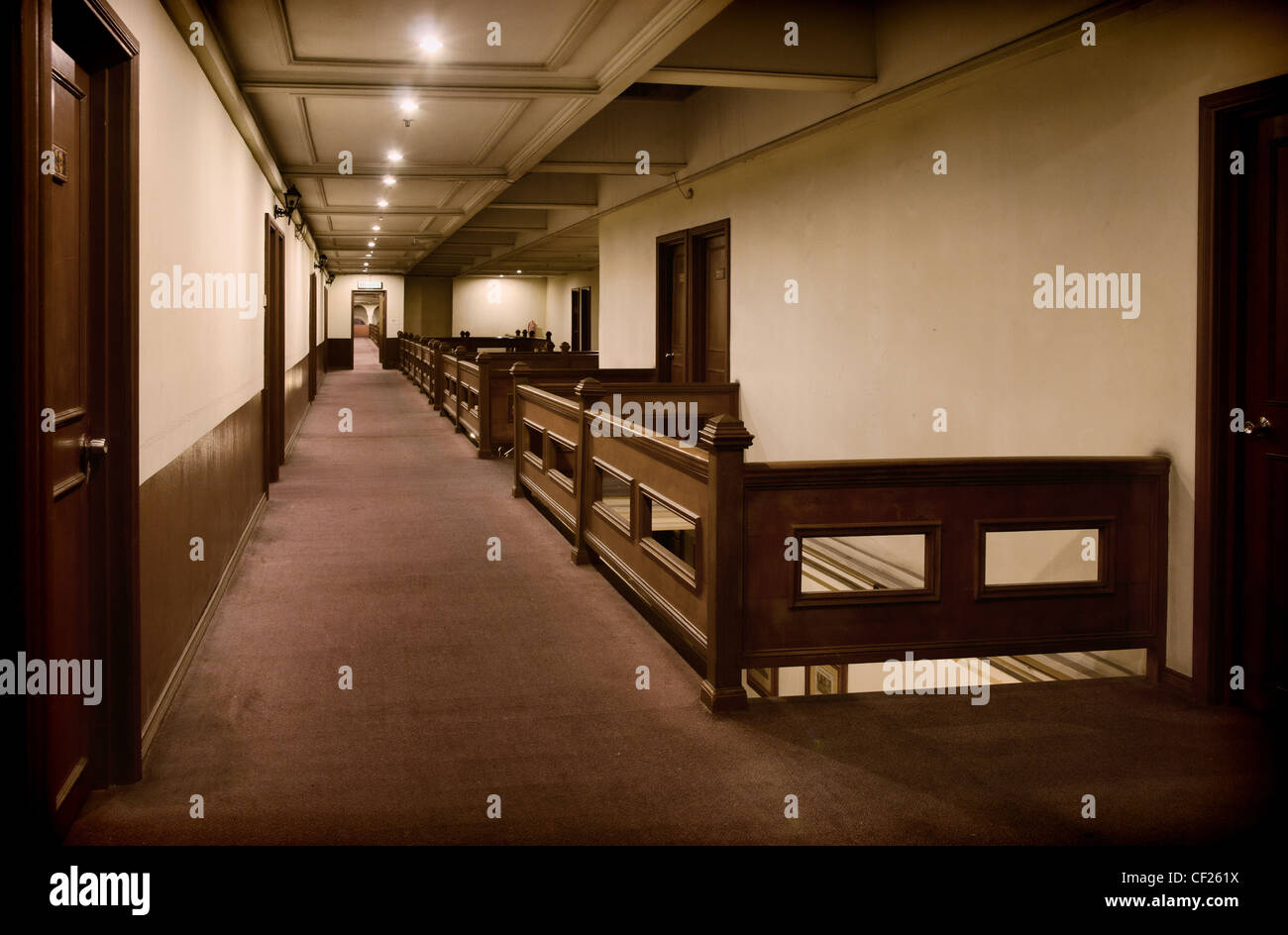 hallway with rooms inside a rough old hotel - Stock Image