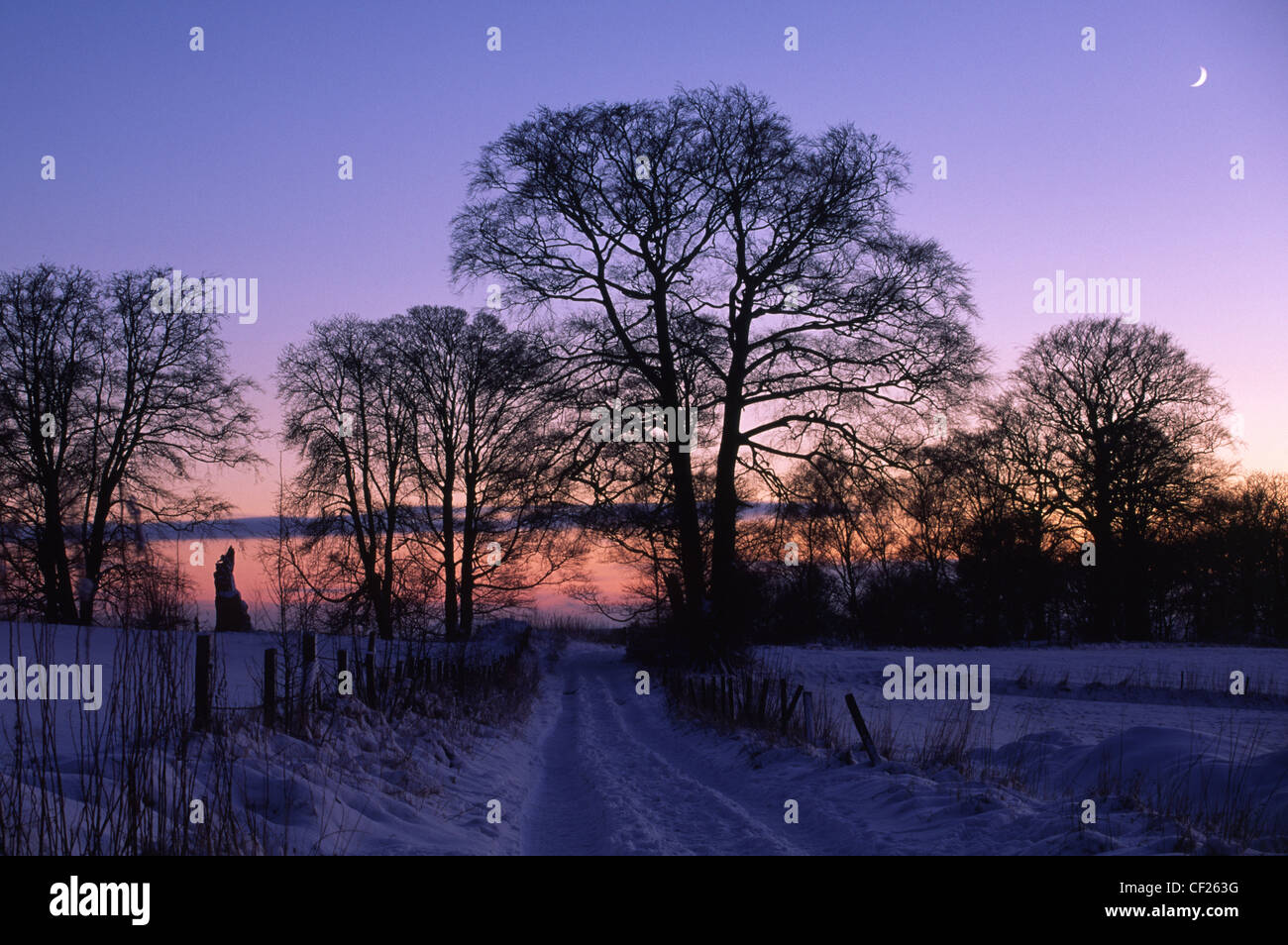 The sun sets behind a country track covered by a winter snow fall. - Stock Image