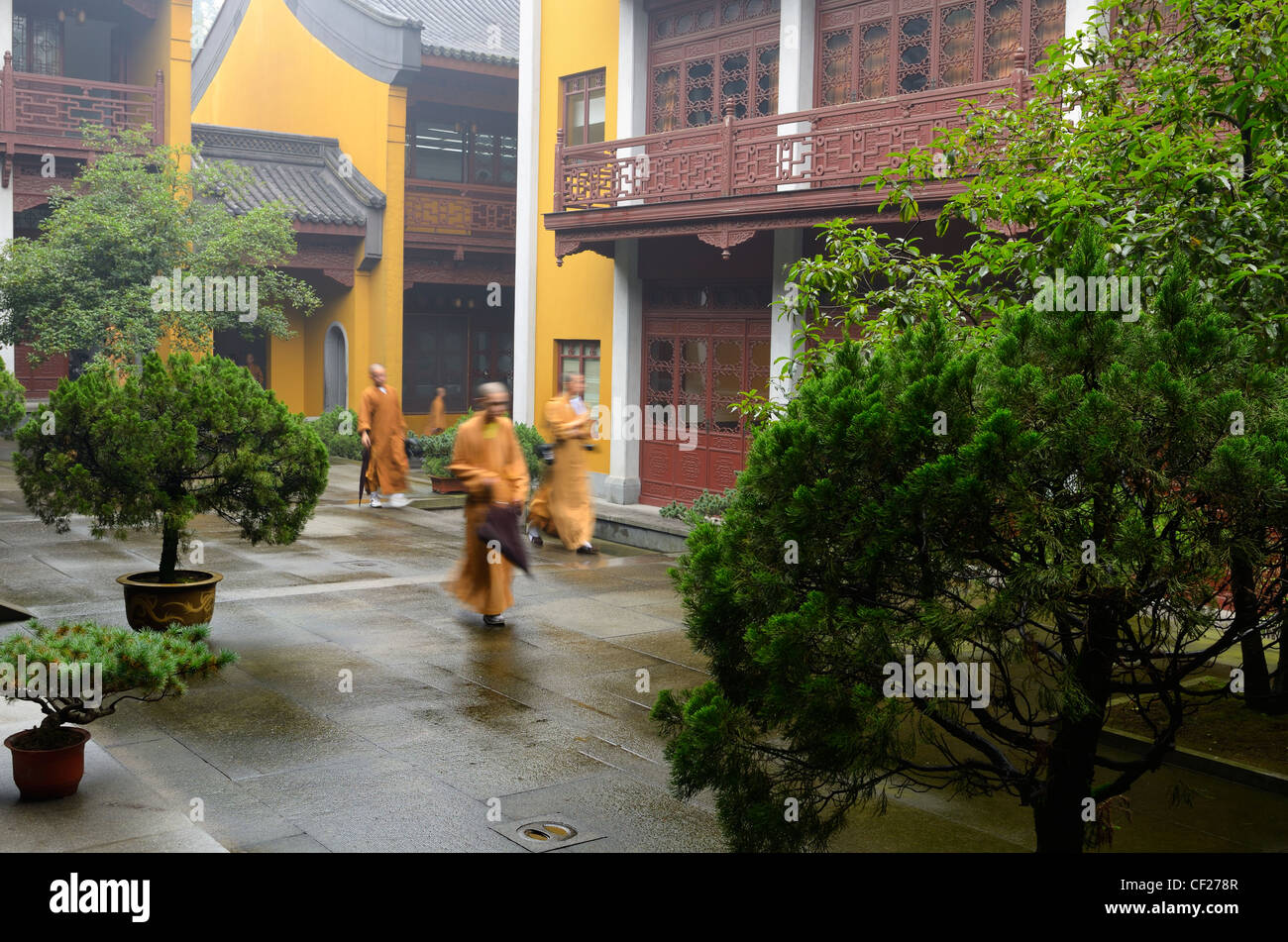 Buddhist monks with umbrella and cameras at the Ling Yin Temple in Hangzhou Peoples Republic of China - Stock Image