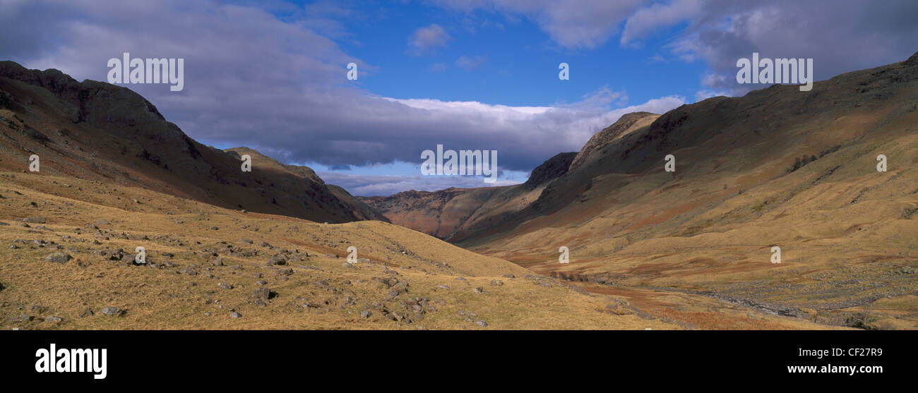 Brief shafts of sun illuminate the surrounding peaks of the Langstrath Valley. - Stock Image