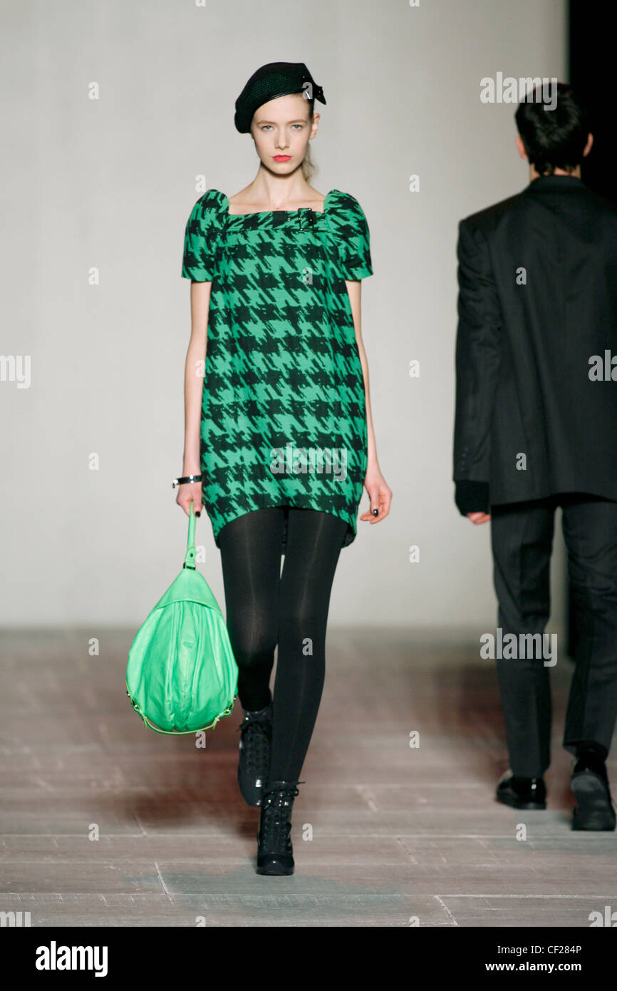 Green and black houndstooth shift dress with green leather pouch bag - Stock Image
