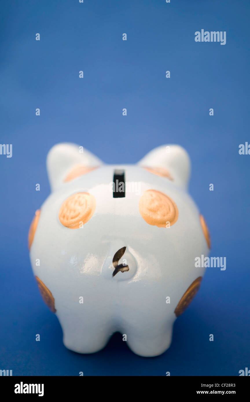 Piggy Bank Against A Blue Background - Stock Image