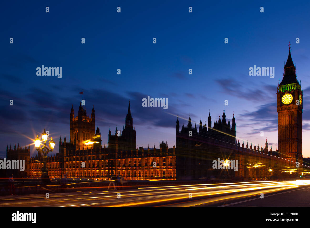 Light trails from traffic passing over Westminster Bridge with Big Ben and the Houses of Parliament in the background. Stock Photo