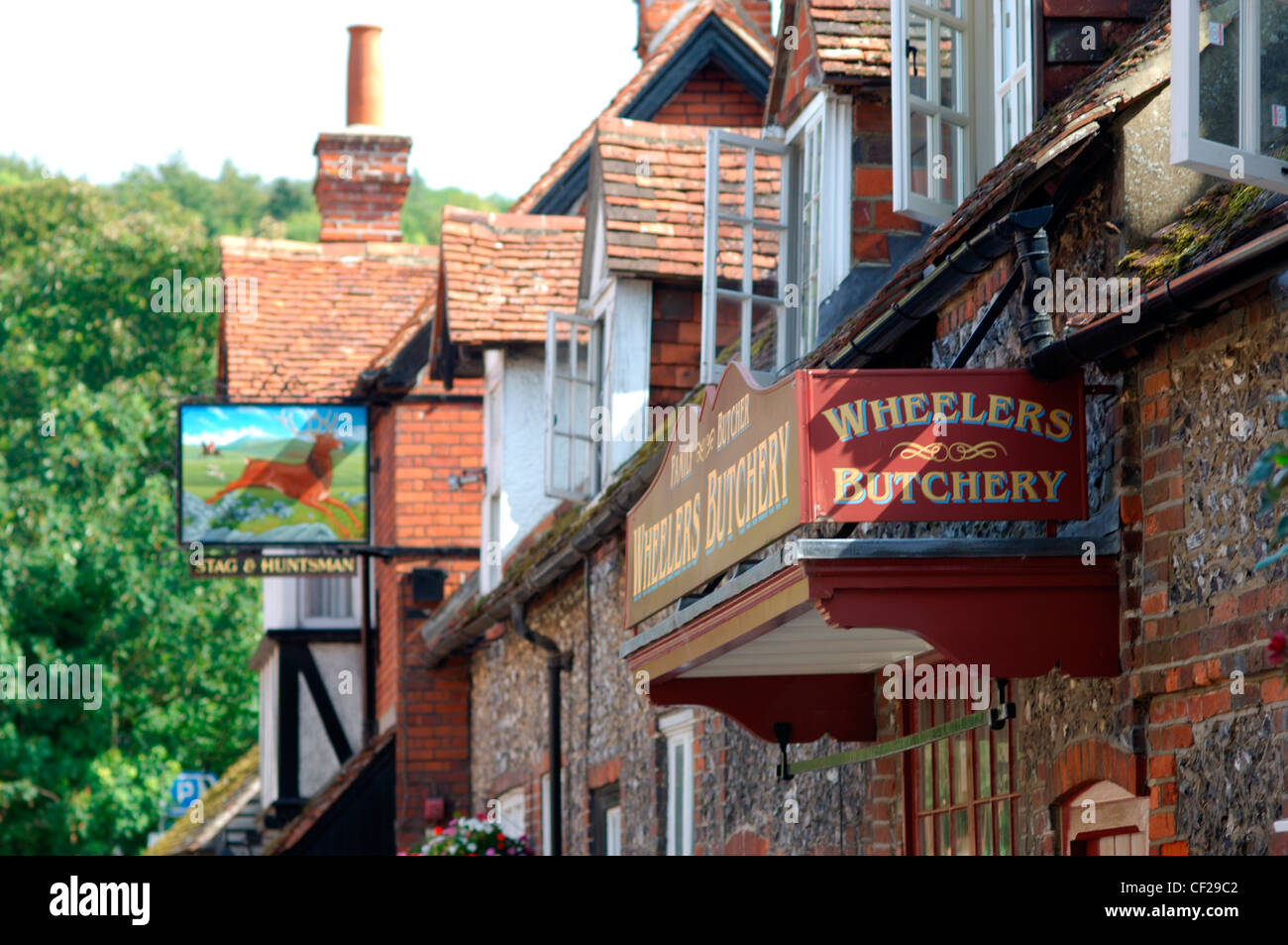 Pub and butcher signs with houses at Hambleden Village. The name is Anglo Saxon in origin and means 'crooked - Stock Image