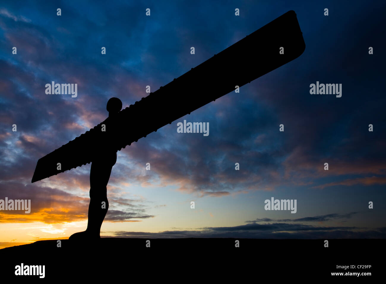 The iconic Angel of the North statue silhouetted against an atmospheric sky. The 'Angel', built on a a former - Stock Image