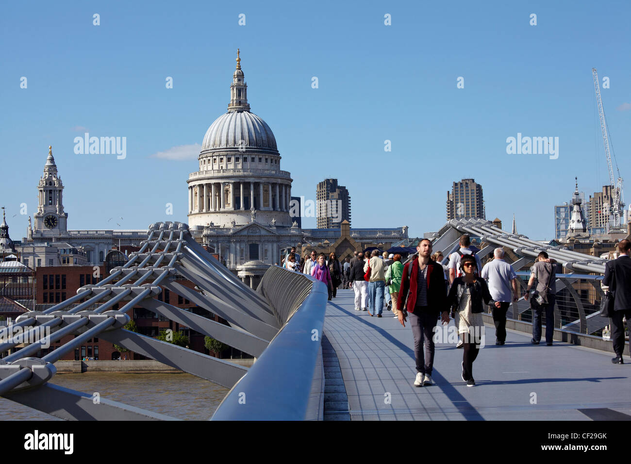 People crossing the Millennium Bridge over the River Thames connecting St Pauls Cathedral on the north bank to Bankside Stock Photo