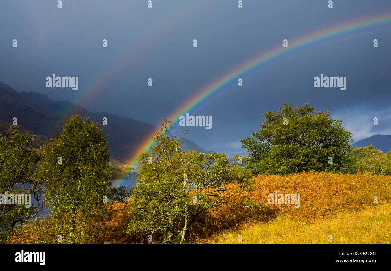 Loch Lomond and the Trossachs National Park. Rainbow over the banks of Loch Lomond and nearby mountains. - Stock Image