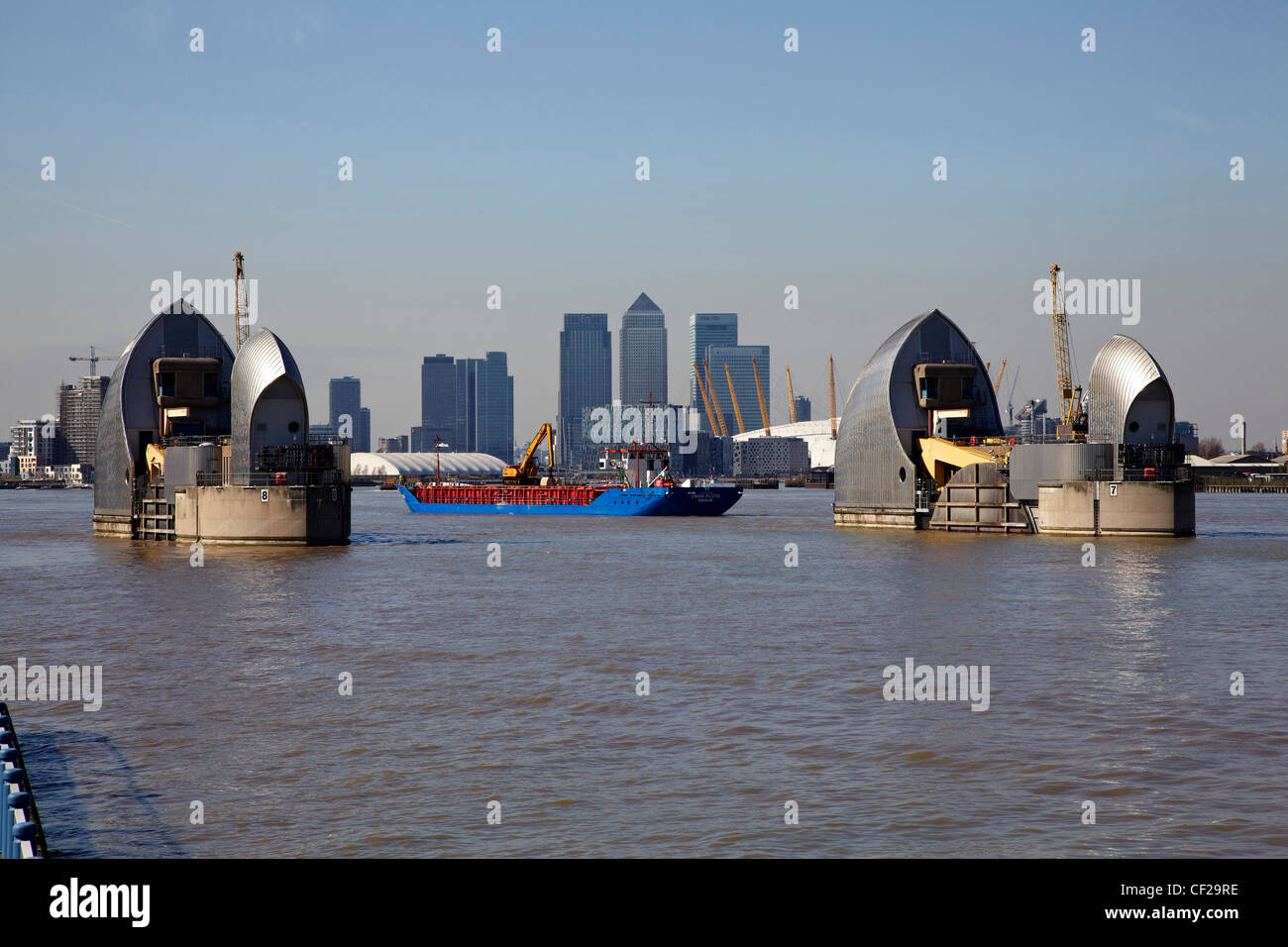 View over the River Thames of the Thames Barrier, O2 and skyscrapers in Canary Wharf. - Stock Image