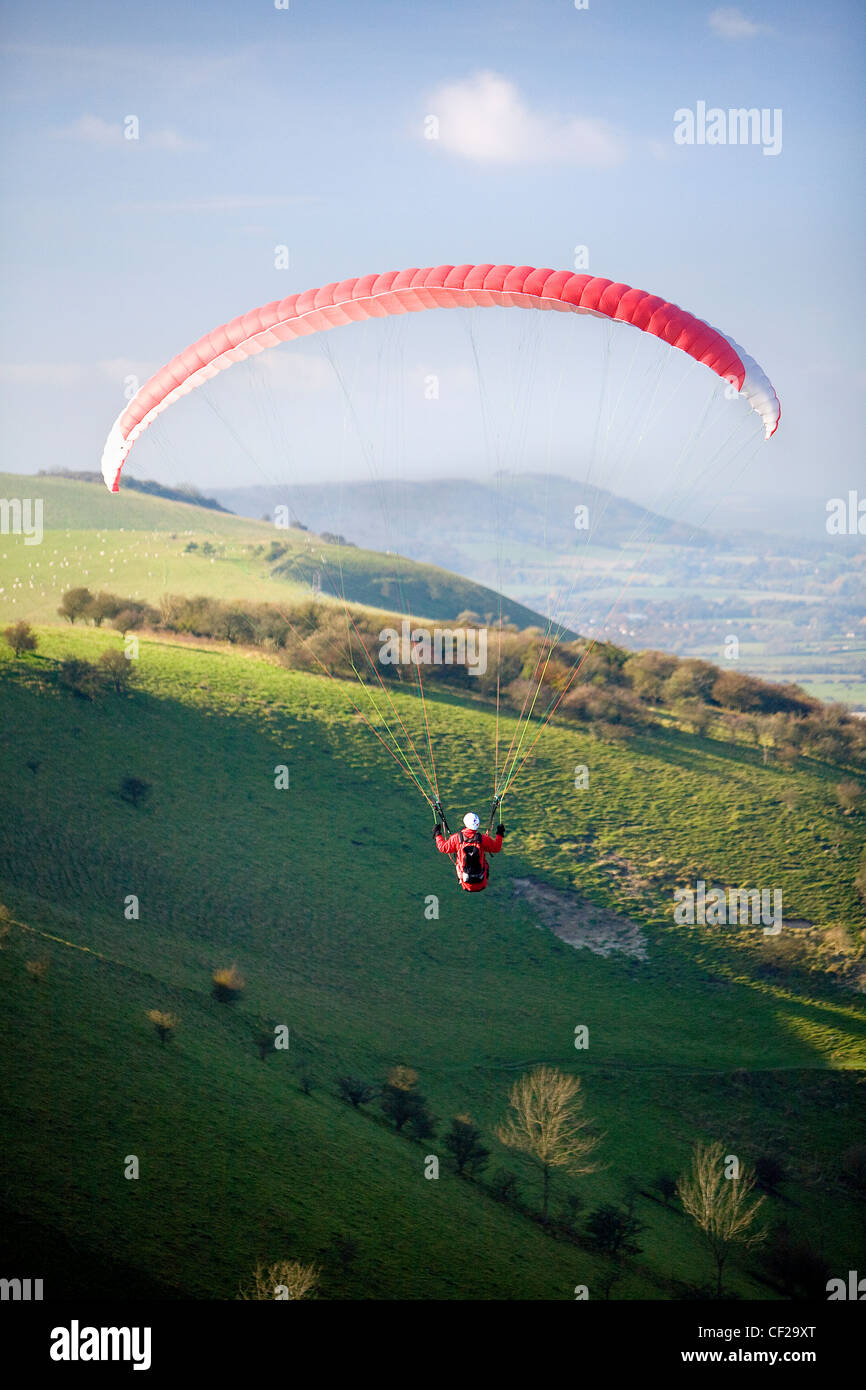 A lone paraglider soars above Devils Dyke on the East Sussex Downs. - Stock Image